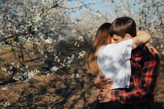 Uomo e donna che abbraccia nel giardino fiorito. le coppie trascorrono del tempo nel giardino primaverile.