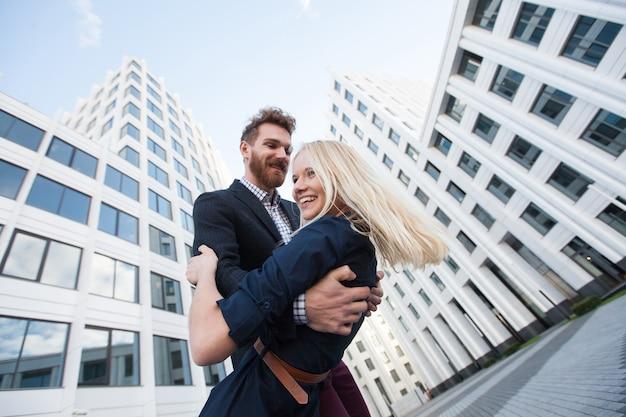 Uomo e donna che si abbracciano e ridono davanti a un edificio bianco. vista dal basso