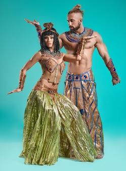 L'uomo e la donna nelle immagini del faraone egiziano e di cleopatra su sfondo blu studio
