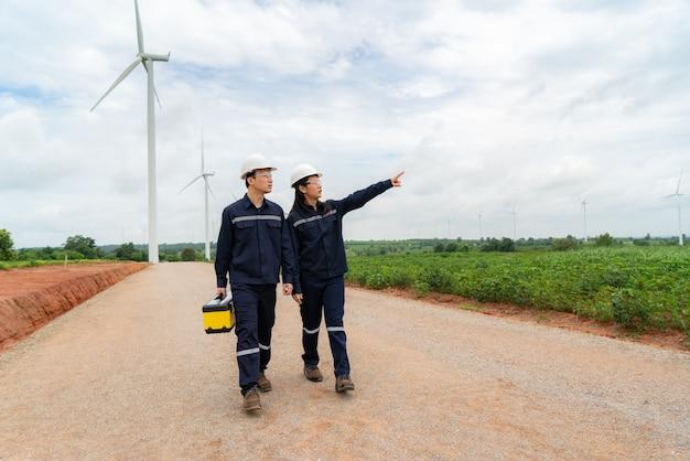Uomo e donna ingegneri di ispezione che preparano e controllano lo stato di avanzamento di una turbina eolica