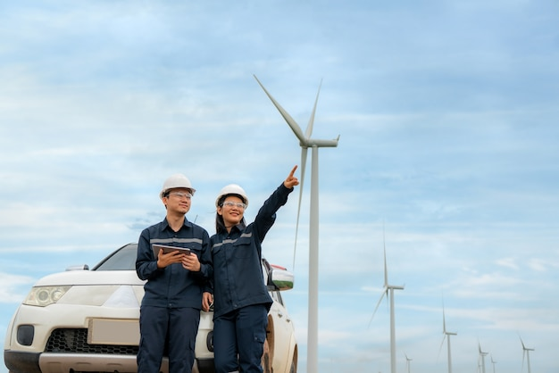 Uomo e donna ingegneri di ispezione preparazione e controllo dei progressi con tavoletta digitale di una turbina eolica