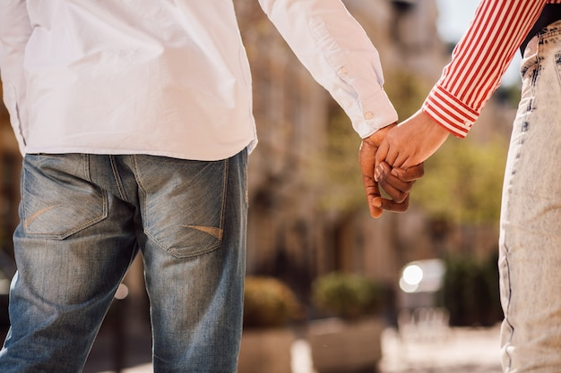 Uomo e donna in jeans e camicie che si tengono per mano