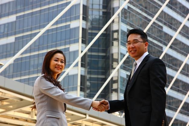 L'uomo e la donna si uniscono le mani dopo aver aderito al business