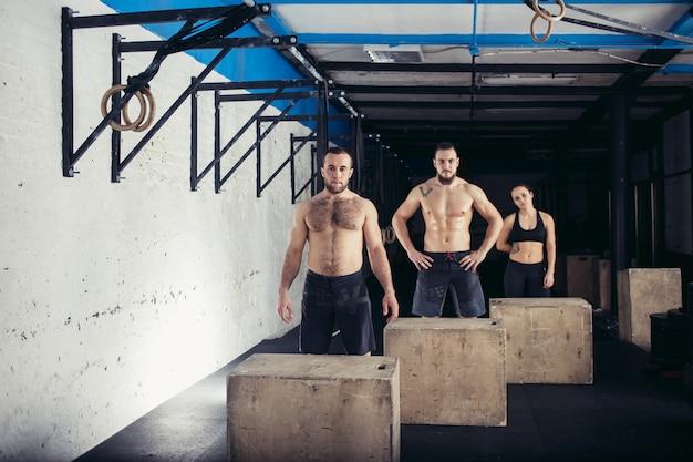 Uomo e donna che saltano sulla scatola in forma in palestra