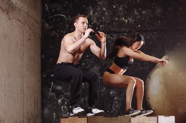 Uomo e donna che saltano sulla scatola in forma
