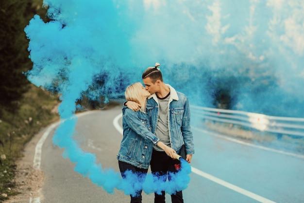 Uomo e donna che bacia sulla strada in montagna con un fumo colorato blu nelle mani.