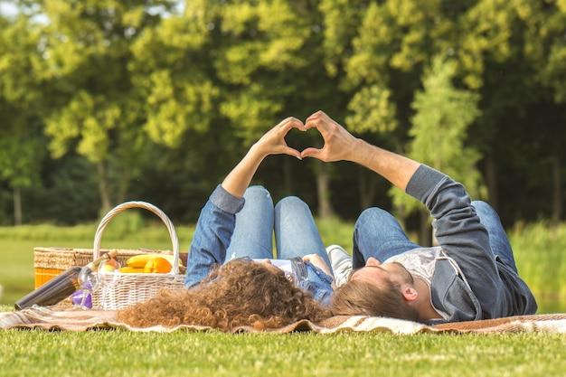 L'uomo e la donna giacciono sull'erba e gesto simbolo d'amore