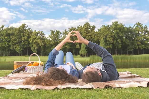 L'uomo e la donna si sdraiano sull'erba e mostrano un segno del cuore