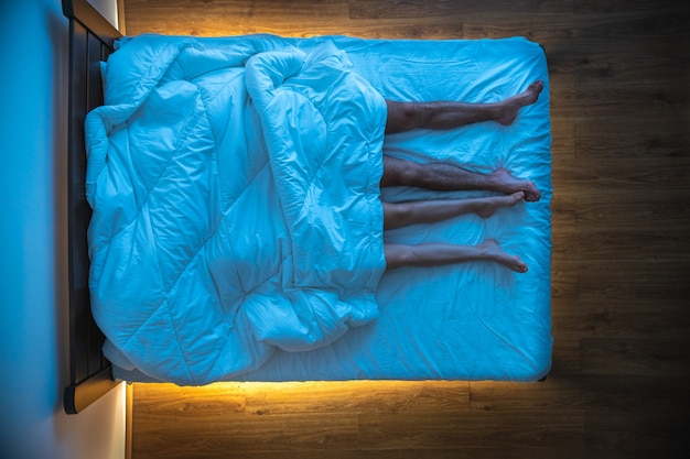 L'uomo e una donna sdraiati sotto una coperta. serale notturno. vista dall'alto
