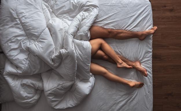L'uomo e una donna sdraiati sotto un piumone. vista dall'alto