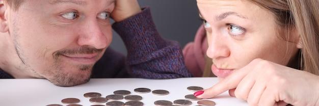 L'uomo e la donna guardano le monete frustrati. concetto di pianificazione del bilancio familiare