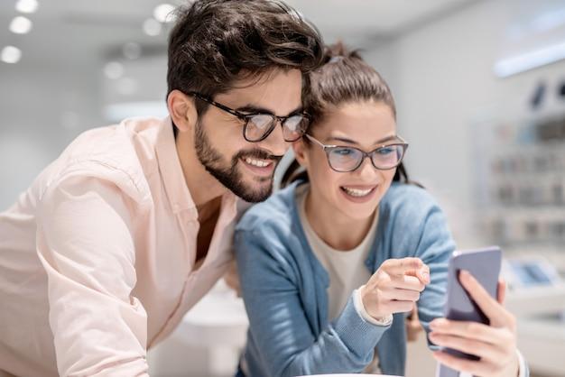 Uomo e donna che esaminano il nuovo smart phone. donna che punta sul telefono.