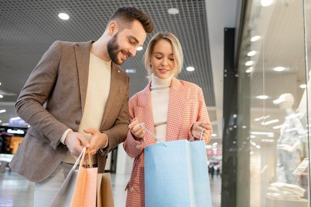 Un uomo e una donna che guardano in un sacchetto di carta durante lo shopping nel centro commerciale