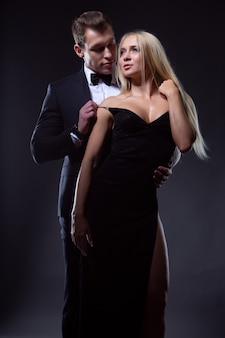 Un uomo e una donna innamorati si abbracciano in abiti da sera alla moda