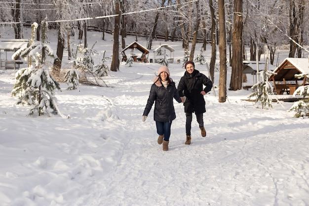 Uomo e donna innamorata che corre su un parco invernale innevato