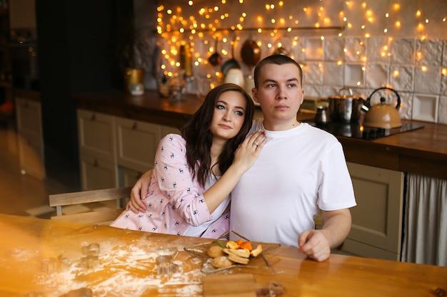 Un uomo e una donna innamorati si siedono in un abbraccio in una cucina in stile loft decorata con luci natalizie
