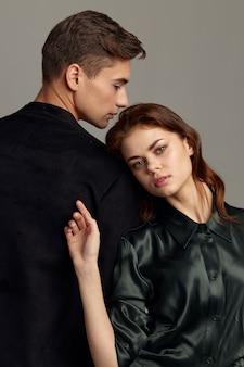 Un uomo e una donna innamorati stanno con le spalle l'un l'altro, vista frontale.