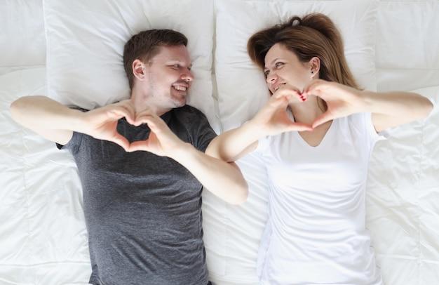 Uomo e donna sdraiata a letto e mostrando il cuore con le loro mani vista dall'alto. concetto di vita familiare