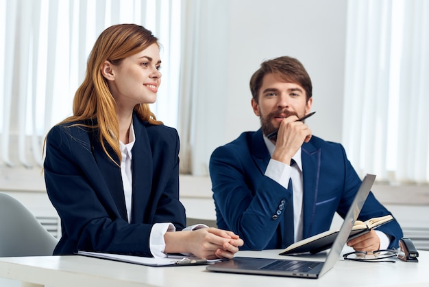 Manager di uomini e donne che parlano al tavolo davanti alla tecnologia del team di laptop