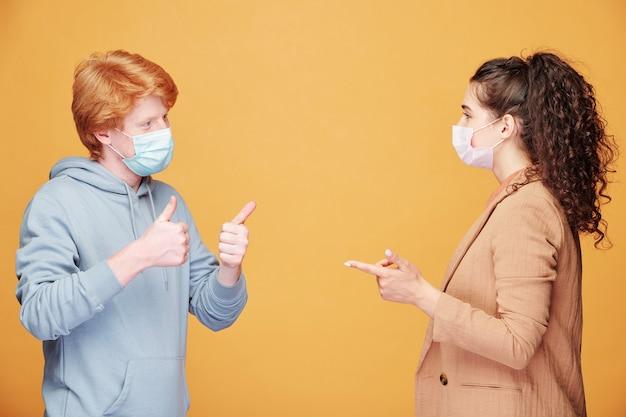 Uomo e donna in maschera medica che parlano