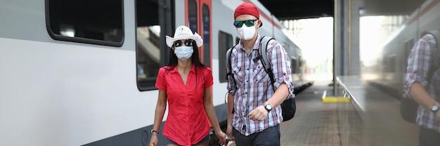 L'uomo e la donna con maschere protettive mediche camminano lungo la piattaforma della stazione