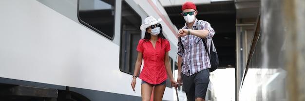 Uomo e donna in maschere protettive mediche camminano lungo il treno con la valigia.