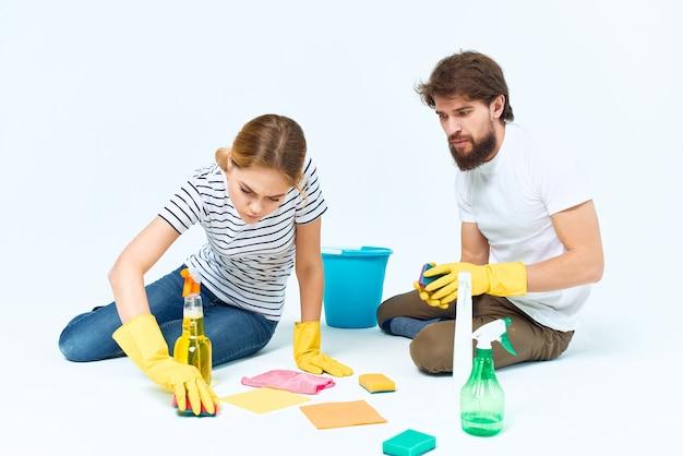 Uomo e donna vicino alla fornitura di servizi di pulizia della stanza del divano