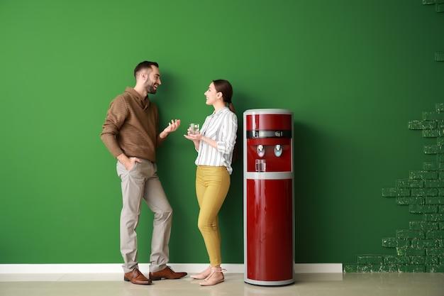 Uomo e donna vicino al dispositivo di raffreddamento dell'acqua contro la parete di colore