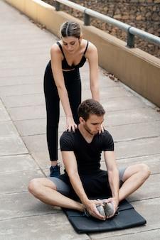Uomo e donna all'aperto che esercitano insieme