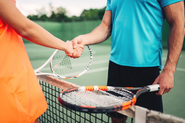 Uomo e donna partner sul campo da tennis all'aperto