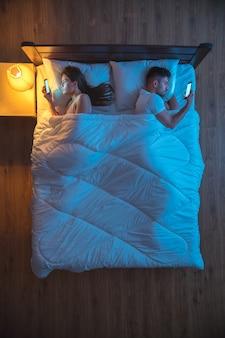 L'uomo e la donna telefonano sul letto. serale notturno. vista dall'alto