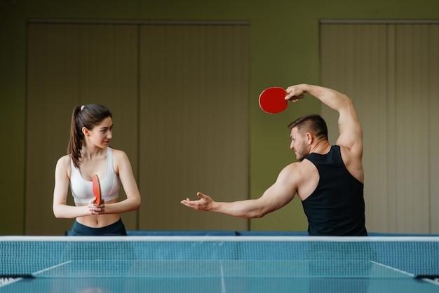 Uomo e donna sulla formazione di ping pong al chiuso.