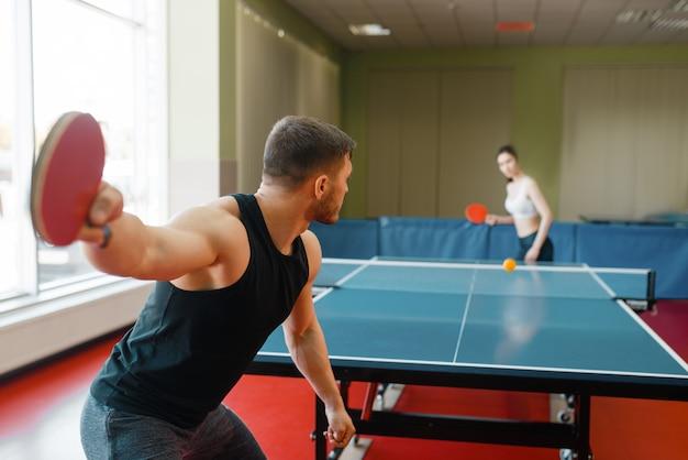 Uomo e donna che giocano a ping pong, concentrarsi sulla racchetta