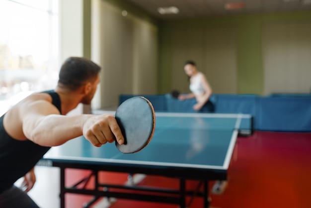 Uomo e donna che giocano a ping pong al chiuso