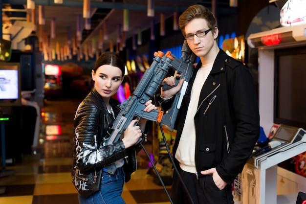 Uomo e donna che giocano sulle attrazioni di slot machine nel centro commerciale
