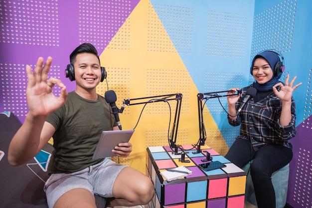 Podcast uomo e donna in studio e mostrando pollice in su
