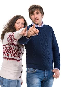 Uomo e donna che punta alla telecamera su un muro bianco