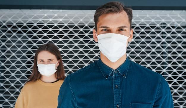Uomo e una donna in maschere protettive in piedi uno accanto all'altro