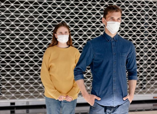 Un uomo e una donna con maschere protettive in piedi a distanza di sicurezza. concetto di tutela della salute.