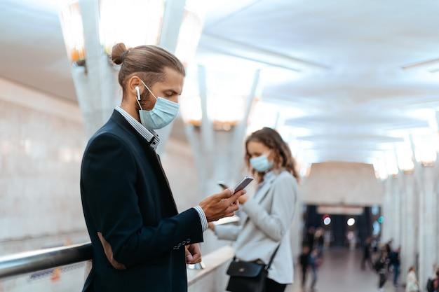 Uomo e donna con maschere protettive in attesa di un treno nella metropolitana