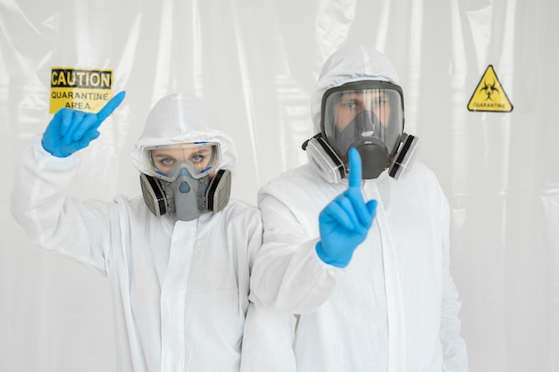 Un uomo e una donna in tute protettive e respiratori, tenendosi la testa durante la quarantena