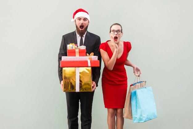 Uomo e donna in abito rosso che tengono regali e pacchi di natale e guardano con faccia meravigliata