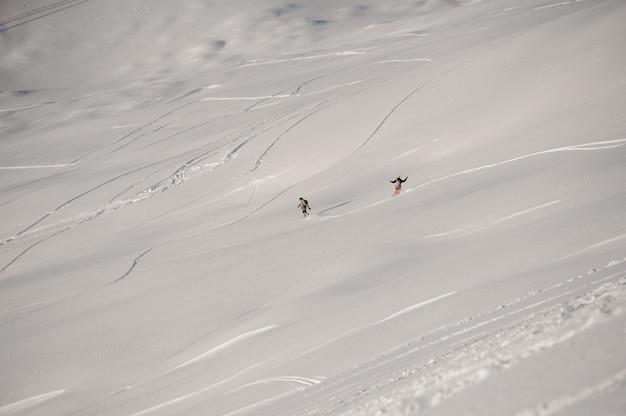 Uomo e donna che guidano giù per la collina sullo snowboard nella famosa località turistica di gudauri in georgia