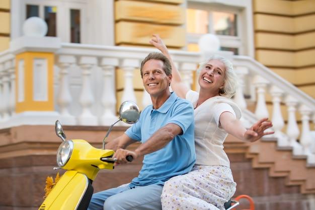 Uomo e donna in sella a uno scooter.