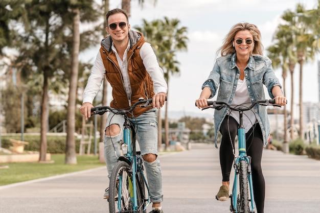 Uomo e donna che guidano le loro bici all'aperto