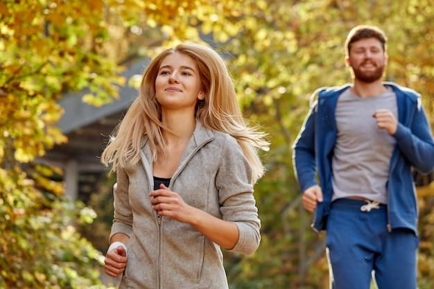 Uomo e donna corrono insieme nella foresta di autunno, uomo sportivo atletico e donna in abiti sportivi