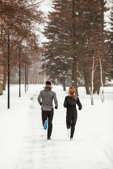 Uomo e donna che corrono nella foresta piena ripresa