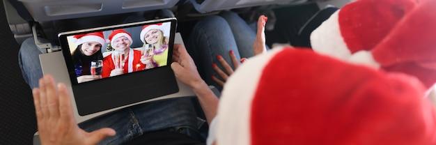 L'uomo e la donna in cappelli di babbo natale augurano felice anno nuovo e buon natale agli amici tramite la scheda digitale...