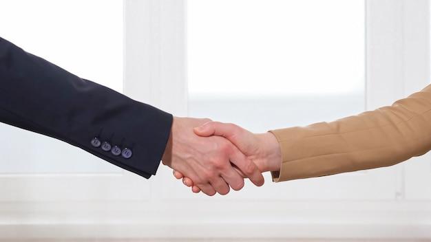 Uomo e donna sigillano un accordo di successo con una stretta di mano vicino alla finestra