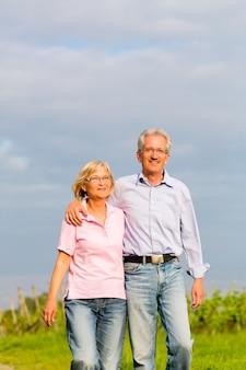 Uomo e donna, coppia senior, passeggiando in estate o all'aperto in vigna